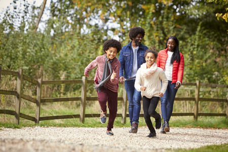 Mixed race children running ahead of their parents on a path during family walk in the countryside, low angle