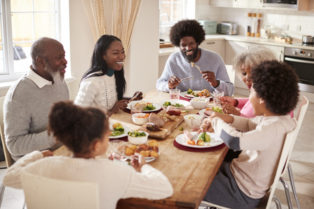 Multi generation mixed race family eating their Sunday dinner together at home, elevated view