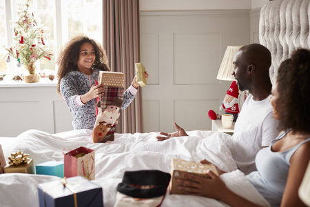 Young mixed race girl giving gifts to her parents on Christmas morning, parents sitting up in bed, close up Stock fotó