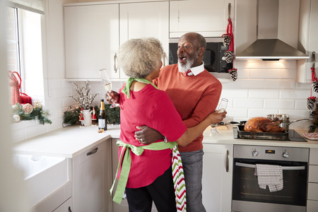 Happy mature black couple holding champagne glasses, laughing and embracing in the kitchen while preparing meal on Christmas morning, close up