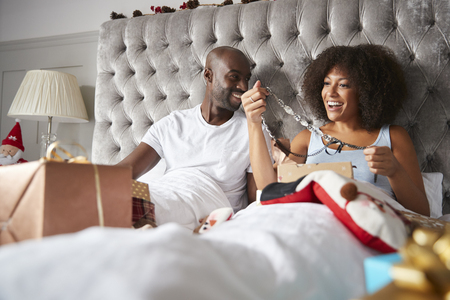 Young adult black woman with her partner opening a present in bed on Christmas morning, low angle