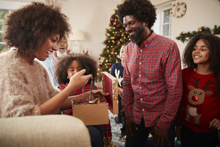 Couple Exchanging Gifts As Multi Generation Family Celebrate Christmas At Home Together