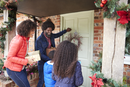 Family Knocking On Front Door As They Arrive For Visit On Christmas Day With Gifts 스톡 콘텐츠 - 115490305