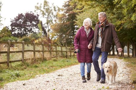 Actief senior koppel op herfstwandeling met hond op pad door platteland