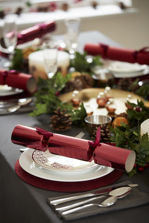 Close up of decorated Christmas table setting, with centrepiece and Christmas crackers arranged on plates