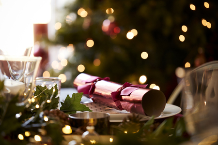 Close up of Christmas table setting with a Christmas cracker arranged on a plate and Christmas tree in the background Stockfoto