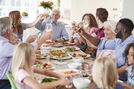 Groupe de famille et d'amis multigénérationnels assis autour d'une table et faisant un toast Banque d'images