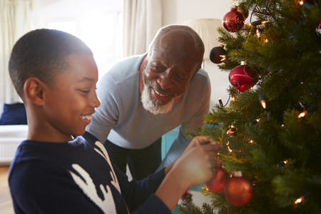 Grandfather And Grandson Hanging Decorations On Christmas Tree At Home Together