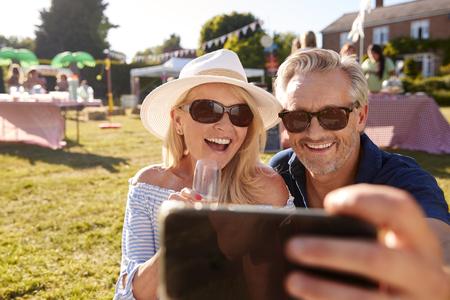 Älteres Paar sitzt auf einem Teppich beim Sommergartenfest unter Selfie auf dem Handy