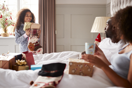 Young mixed race girl carrying gifts in her parentsÕ bedroom on Christmas morning, parents sitting up in bed, close up
