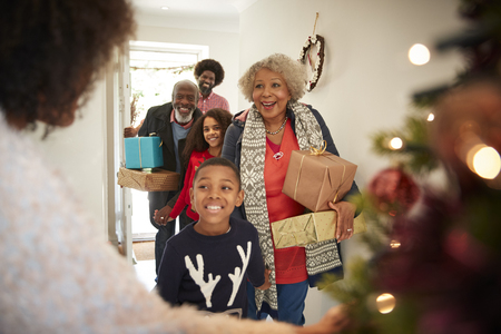 Grandparents Being Greeted By Family As They Arrive For Visit On Christmas Day With Gifts 스톡 콘텐츠 - 115490303