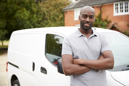 Young black adult tradesman standing next to his white van, close up, close up Stockfoto