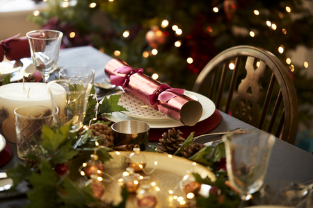 Christmas table setting with a Christmas cracker arranged on a plate with red and green table decorations and a Christmas tree in the background Imagens