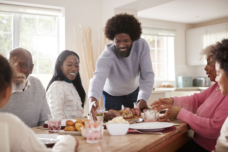 Middle aged black man bringing roast meat to the table for the Sunday family dinner with his partner, kids and their grandparents, front view