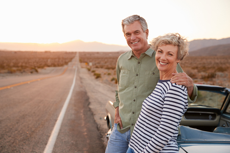 Senior couple on road trip standing by car smiling to camera 写真素材