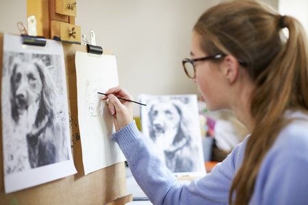 Female Teenage Artist Sitting At Easel Drawing Picture Of Dog From Photograph In Charcoal Imagens