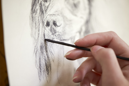 Close Up Of Artist Sitting At Easel Drawing Picture Of Dog In Charcoal 免版税图像