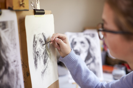 Side View Of Female Teenage Artist Sitting At Easel Drawing Picture Of Dog From Photograph In Charcoal Stock Photo - 113627834