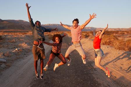 Amigos adultos jóvenes divirtiéndose saltando en el desierto