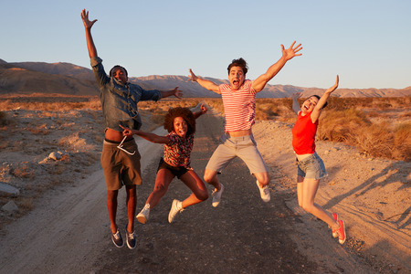 Young adult friends having fun jumping in the desert 스톡 콘텐츠