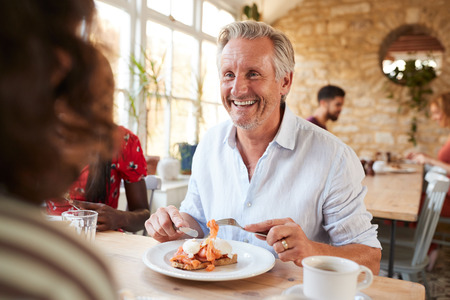 Happy senior white man eating brunch with friends at a cafe Фото со стока
