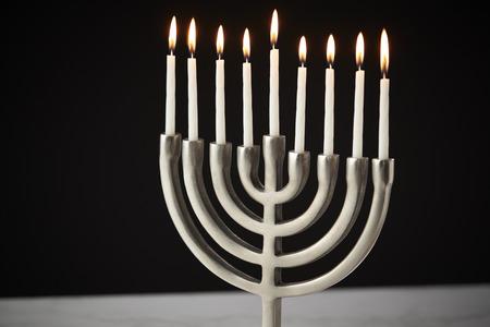 Lit Candles On Metal Hanukkah Menorah On Marble Surface Against Black Studio Background Stock Photo