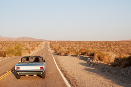 Couple driving convertible car on desert highway, back view