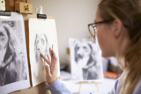 Side View Of Female Teenage Artist Sitting At Easel Drawing Picture Of Dog From Photograph In Charcoal