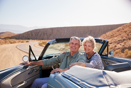 Senior couple smile to camera from parked open top car Imagens