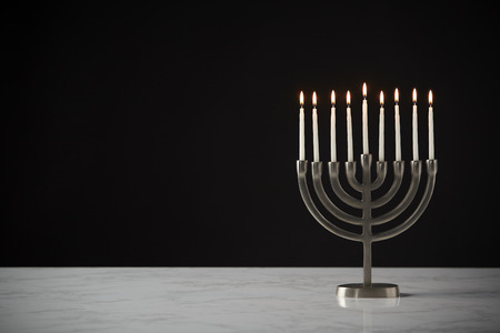 Lit Candles On Metal Hanukkah Menorah On Marble Surface Against Black Studio Background Stockfoto