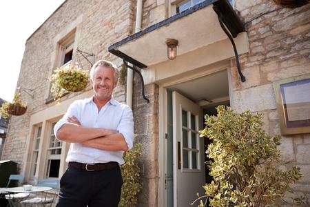 Älterer männlicher Restaurant-Pub-Besitzer steht vor dem Eingang