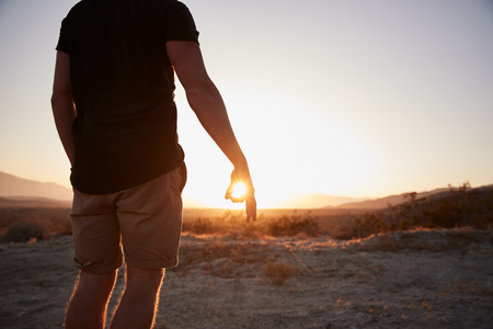 Man in desert circling setting sun with fingers, mid section