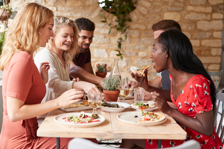 Jonge volwassen vrienden lunchen aan een tafel in een restaurant