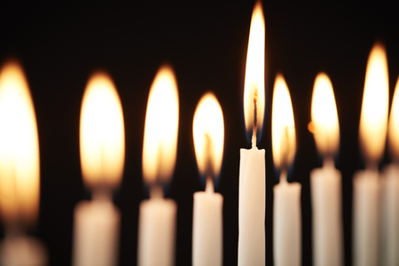 Close Up Of Lit Candles On Metal Hanukkah Menorah Against Black Studio Background Stock Photo