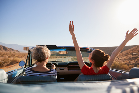 Mum driving car, daughter with hands in the air, back view Stock Photo
