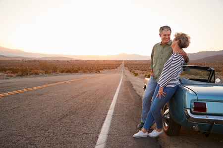 Senior couple on road trip standing by car, full length Stock Photo