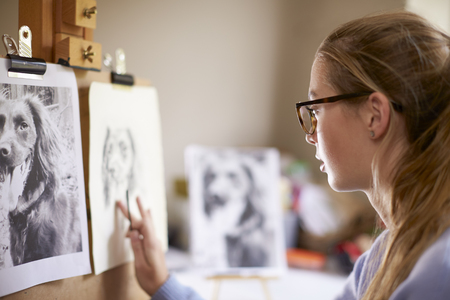 Side View Of Female Teenage Artist Sitting At Easel Drawing Picture Of Dog From Photograph In Charcoal Фото со стока - 113628042