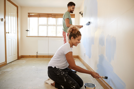 Paar schmückt Zimmer in neuem Haus, das zusammen Wand malt