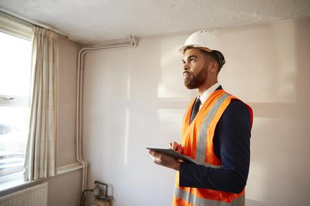 Topógrafo con casco y chaqueta de alta visibilidad con tableta digital que realiza la inspección de la casa