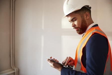 Gutachter mit Schutzhelm und Warnweste mit digitalem Tablet bei der Hausinspektion Standard-Bild