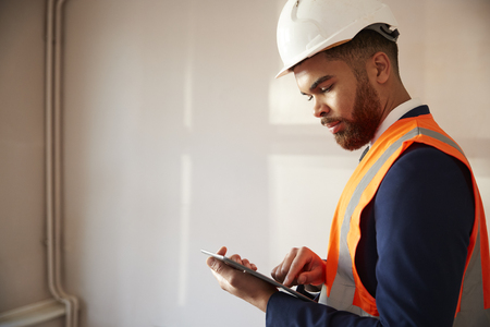 Landmeter in bouwvakker en hoge zichtbaarheidsjas met digitale tablet die huisinspectie uitvoert Stockfoto