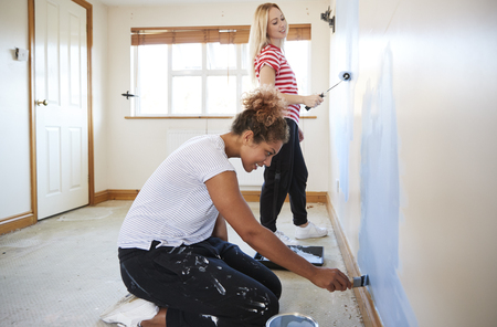 Two Women Decorating Room In New Home Painting Wall