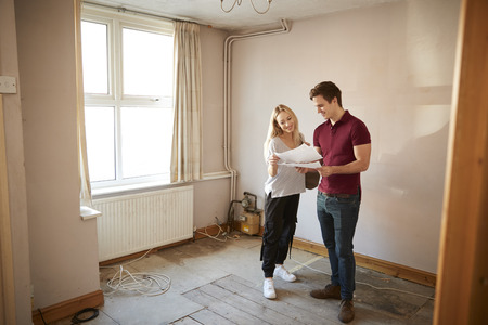 Couple Buying House For First Time Looking At House Survey In Room To Be Renovated