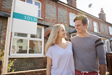 Excited Couple Standing Outside New Home With Sold Sign 写真素材
