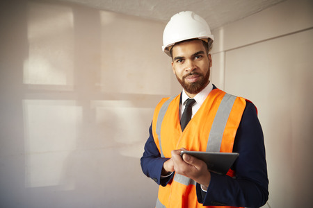 Portrait Of Surveyor In Hard Hat And High Visibility Jacket With Digital Tablet Carrying Out House Inspection Stock Photo