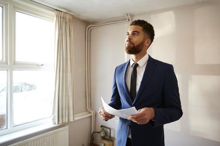 Mannelijke makelaar die naar huisdetails kijkt in onroerend goed voor renovatie