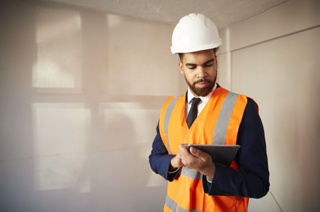 Surveyor In Hard Hat And High Visibility Jacket With Digital Tablet Carrying Out House Inspection Stock Photo