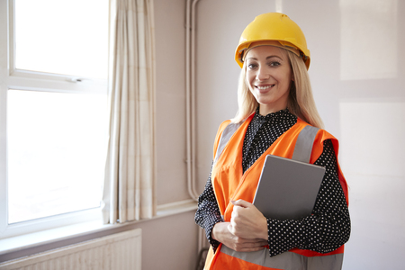 Portrait Of Female Surveyor In Hard Hat And High Visibility Jacket With Digital Tablet Carrying Out House Inspection Stock Photo