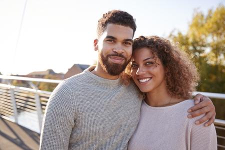 Portrait Of Young Couple Walking Across City Bridge Together
