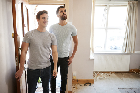 Excited Male Couple Opening Front Door Of New Home